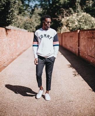 Moda uomo anni 20: Coniuga una felpa stampata bianca con chino grigio scuro per un look semplice, da indossare ogni giorno. Sneakers basse di tela bianche sono una gradevolissima scelta per completare il look.