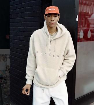 Come indossare: felpa con cappuccio di pile beige, t-shirt girocollo beige, pantaloni sportivi bianchi, berretto da baseball rosso