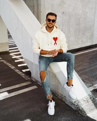 Come indossare e abbinare: felpa con cappuccio stampata bianca, jeans aderenti strappati blu, sneakers basse in pelle bianche e nere, occhiali da sole neri