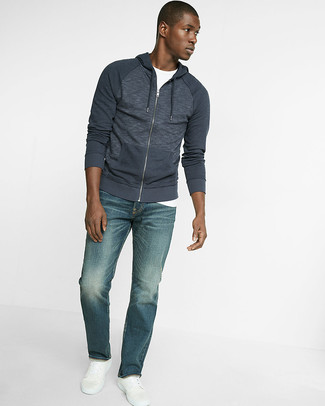 Come indossare: felpa con cappuccio blu scuro, t-shirt girocollo bianca, jeans blu, sneakers basse in pelle bianche