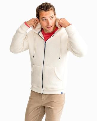 Come indossare: felpa con cappuccio di pile beige, t-shirt manica lunga rossa, chino marrone chiaro