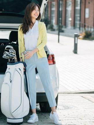 Come indossare e abbinare: felpa con cappuccio gialla, polo bianco, pantaloni stretti in fondo azzurri, sneakers basse in pelle bianche
