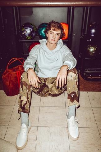 Come indossare e abbinare: felpa con cappuccio grigia, pantaloni sportivi mimetici marrone chiaro, sneakers basse in pelle bianche, calzini grigi