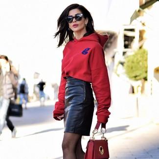 Come indossare: felpa con cappuccio rossa, minigonna in pelle nera, cartella in pelle rossa, occhiali da sole neri