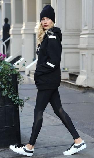 Come indossare: felpa con cappuccio nera, leggings neri, sneakers basse in pelle bianche e nere, cuffia nero