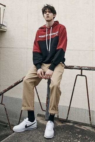Moda ragazzo adolescente: Abbina una felpa con cappuccio stampata rossa con chino marrone chiaro per un pranzo domenicale con gli amici. Per distinguerti dagli altri, prova con un paio di scarpe sportive bianche e nere.