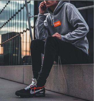 Trend da uomo 2020: Abbina una felpa con cappuccio stampata grigia con jeans aderenti neri per un look perfetto per il weekend. Scarpe sportive nere e bianche sono una splendida scelta per completare il look.