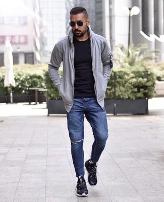 Come indossare e abbinare: felpa con cappuccio grigia, t-shirt girocollo nera, jeans strappati blu scuro, scarpe sportive nere