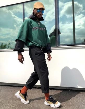 Come indossare e abbinare: felpa stampata verde, felpa con cappuccio nera, chino neri, scarpe sportive gialle