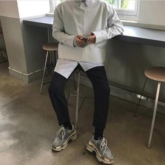 Come indossare e abbinare: felpa grigia, camicia a maniche lunghe bianca, chino neri, scarpe sportive grigie
