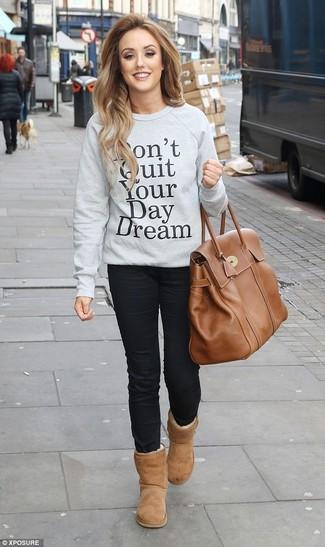 Come indossare: felpa stampata grigia, jeans aderenti neri, stivali ugg marrone chiaro, borsa shopping in pelle marrone