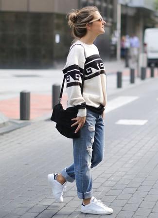 Come indossare e abbinare: felpa stampata bianca e nera, jeans boyfriend strappati blu, sneakers basse in pelle bianche, borsa a tracolla in pelle scamosciata nera