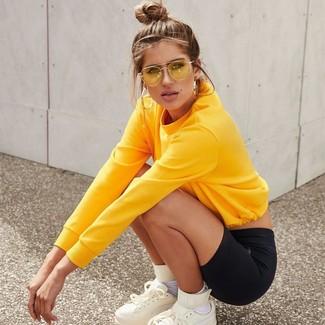 Come indossare e abbinare: felpa gialla, pantaloncini ciclisti neri, sneakers alte in pelle bianche, calzini bianchi