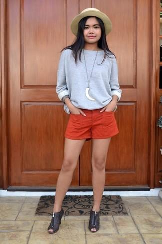 Come indossare e abbinare: felpa grigia, pantaloncini arancioni, stivaletti in pelle tagliati marrone scuro, borsalino di paglia marrone chiaro