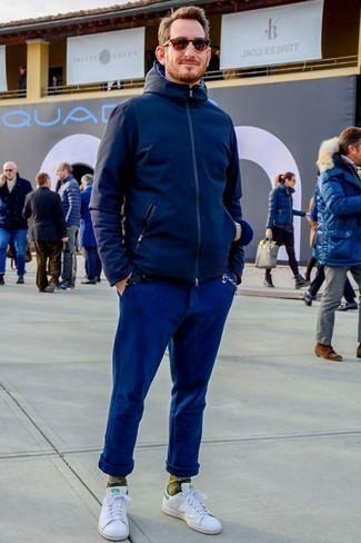 Trend da uomo 2020: Combina una giacca a vento blu scuro con chino blu scuro per un look semplice, da indossare ogni giorno. Sneakers basse in pelle bianche sono una splendida scelta per completare il look.