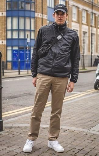 Come indossare e abbinare un marsupio in pelle nero: Indossa una giacca a vento nera con un marsupio in pelle nero per una sensazione di semplicità e spensieratezza. Opta per un paio di sneakers basse in pelle bianche per mettere in mostra il tuo gusto per le scarpe di alta moda.
