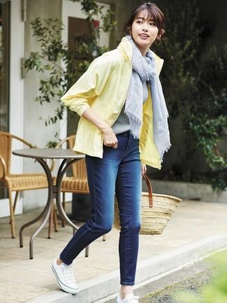 Come indossare: giacca a vento gialla, jeans aderenti blu scuro, sneakers basse di tela bianche, borsa shopping di paglia marrone chiaro