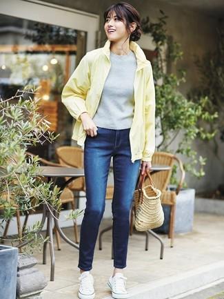Come indossare: giacca a vento gialla, maglione a maniche corte grigio, jeans aderenti blu scuro, sneakers basse di tela bianche