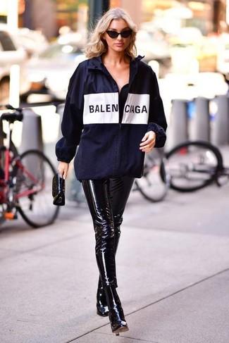 Come indossare: giacca a vento stampata blu scuro, pantaloni skinny in pelle neri, stivaletti in pelle neri, pochette in pelle nera
