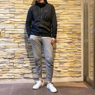 Come indossare e abbinare: giacca a vento nera, t-shirt girocollo bianca, pantaloni sportivi grigi, sneakers basse bianche