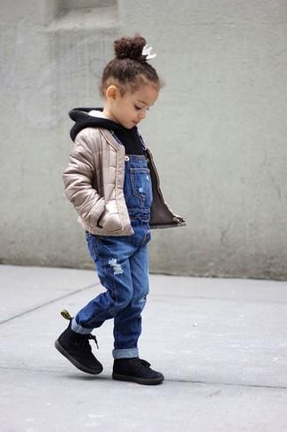 Come indossare: giacca trapuntata beige, felpa con cappuccio nera, salopette di jeans blu, stivali neri