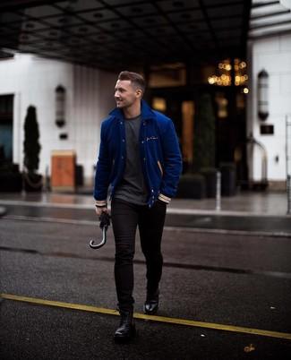 Come indossare e abbinare: giacca college blu, t-shirt girocollo grigio scuro, jeans aderenti neri, stivali casual in pelle neri