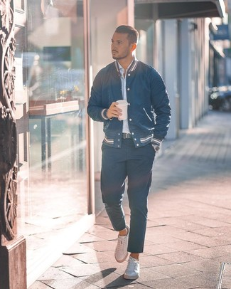Come indossare e abbinare: giacca college blu scuro, camicia a maniche lunghe a righe verticali azzurra, chino blu scuro, sneakers basse in pelle bianche