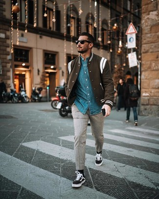 Come indossare e abbinare: giacca college nera e bianca, camicia di jeans blu, chino di lana grigi, sneakers basse di tela nere e bianche