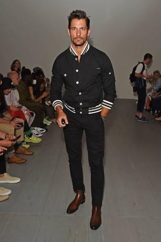 Look alla moda per uomo: Giacca college nera, Chino neri, Stivali chelsea in pelle marroni, Orologio nero e bianco