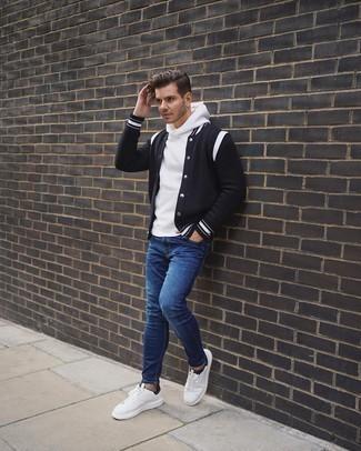 Come indossare e abbinare jeans aderenti blu: Indossa una giacca college nera e bianca con jeans aderenti blu per un look comfy-casual. Ti senti creativo? Completa il tuo outfit con un paio di sneakers basse di tela bianche e nere.