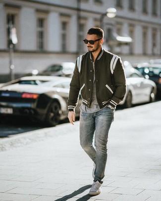 Come indossare e abbinare: giacca college nera e bianca, t-shirt girocollo grigia, jeans azzurri, sneakers basse bianche