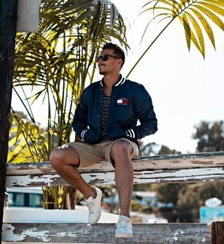 Come indossare e abbinare: giacca college blu scuro, t-shirt girocollo a righe orizzontali nera e bianca, pantaloncini marrone chiaro, sneakers basse in pelle bianche