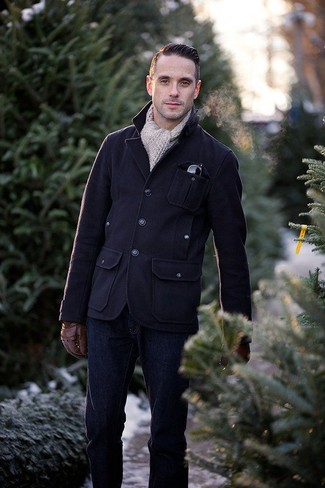 Come indossare e abbinare: giacca da campo di lana blu scuro, jeans blu scuro, sciarpa lavorata a maglia beige, guanti in pelle marroni