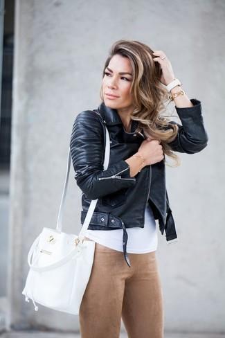 Come indossare: giacca da moto in pelle nera, canotta bianca, leggings in pelle scamosciata marrone chiaro, borsa a secchiello in pelle bianca