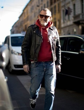 Moda uomo anni 50: Potresti abbinare una giacca da moto in pelle nera con jeans strappati blu per una sensazione di semplicità e spensieratezza. Scegli uno stile classico per le calzature e calza un paio di sneakers basse di tela nere e bianche.