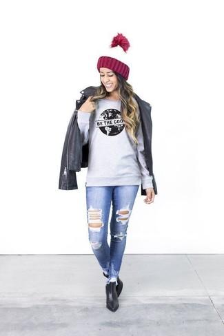 Come indossare: giacca da moto in pelle nera, felpa stampata grigia, jeans aderenti strappati blu, stivaletti in pelle neri