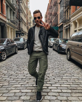 Come indossare e abbinare: giacca da moto in pelle nera, felpa grigia, pantaloni cargo verde oliva, scarpe sportive nere