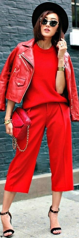 Come indossare: giacca da moto in pelle rossa, maglione a maniche corte rosso, pinocchietti rossi, sandali con tacco in pelle scamosciata leopardati neri