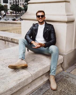 Come indossare e abbinare: giacca da moto in pelle nera, maglione a trecce bianco, jeans aderenti azzurri, stivali chelsea in pelle scamosciata beige