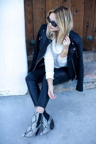 Come indossare: giacca da moto in pelle nera, maglione con scollo a cappuccio bianco, pantaloni skinny in pelle neri, stivaletti in pelle con stampa serpente grigi