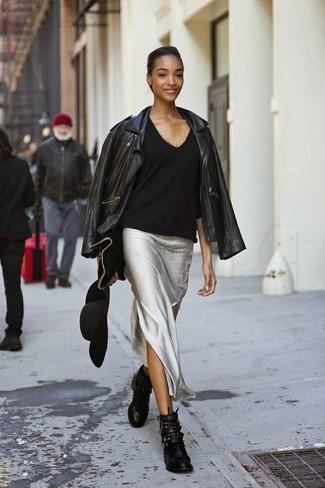 Una giacca da moto in pelle nera e una gonna lunga argento metteranno in luce il tuo gusto per gli abiti di sartoria. Mostra il tuo gusto per le calzature di alta classe con un paio di stivaletti in pelle con borchie neri per donna di Alexander McQueen.