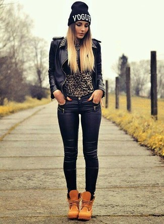 Come indossare e abbinare: giacca da moto in pelle con borchie nera, maglione girocollo leopardato marrone, jeans aderenti in pelle neri, stivali piatti stringati in nubuck marrone chiaro