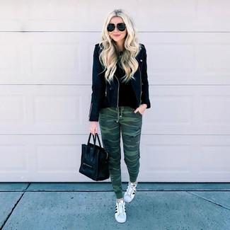 Come indossare: giacca da moto in pelle nera, maglione girocollo nero, pantaloni sportivi mimetici verde scuro, sneakers basse in pelle bianche e nere