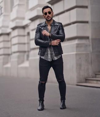 Come indossare e abbinare: giacca da moto in pelle nera, camicia a maniche corte con stampa serpente grigia, jeans aderenti strappati neri, stivali chelsea in pelle neri