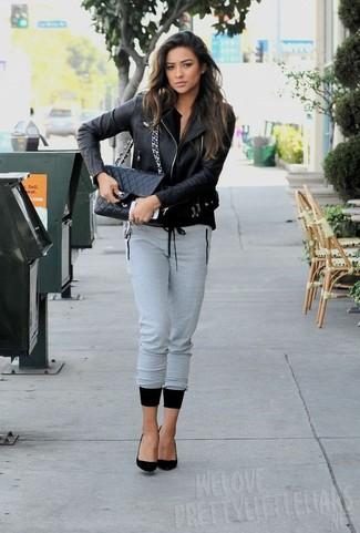 Se sei tipo da jeans e maglietta, ti piacerà questo semplice abbinamento di una giacca da moto in pelle nera e pantaloni sportivi grigi. Aggiungi un paio di décolleté in pelle scamosciata neri al tuo look per migliorare all'istante il tuo stile.