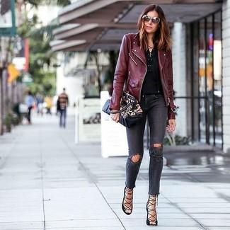 Come indossare: giacca da moto in pelle bordeaux, serafino nero, jeans aderenti strappati grigio scuro, sandali gladiatore in pelle neri