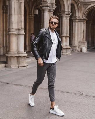 Come indossare e abbinare: giacca da moto in pelle nera, t-shirt girocollo stampata bianca e nera, chino a righe verticali grigi, sneakers basse in pelle bianche e nere