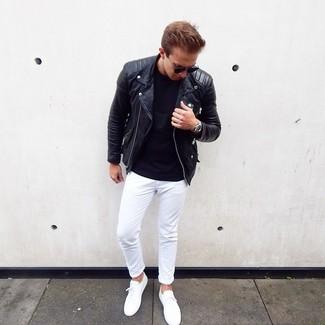 Come indossare e abbinare: giacca da moto in pelle nera, t-shirt girocollo nera, chino bianchi, sneakers basse bianche