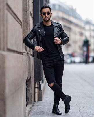 Come indossare e abbinare: giacca da moto in pelle nera, t-shirt girocollo nera, jeans aderenti strappati neri, stivali chelsea in pelle neri