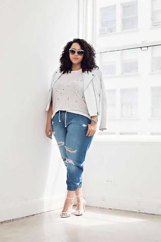 Come indossare e abbinare: giacca da moto in pelle bianca, t-shirt girocollo beige, jeans strappati blu, sandali con tacco in pelle bianchi